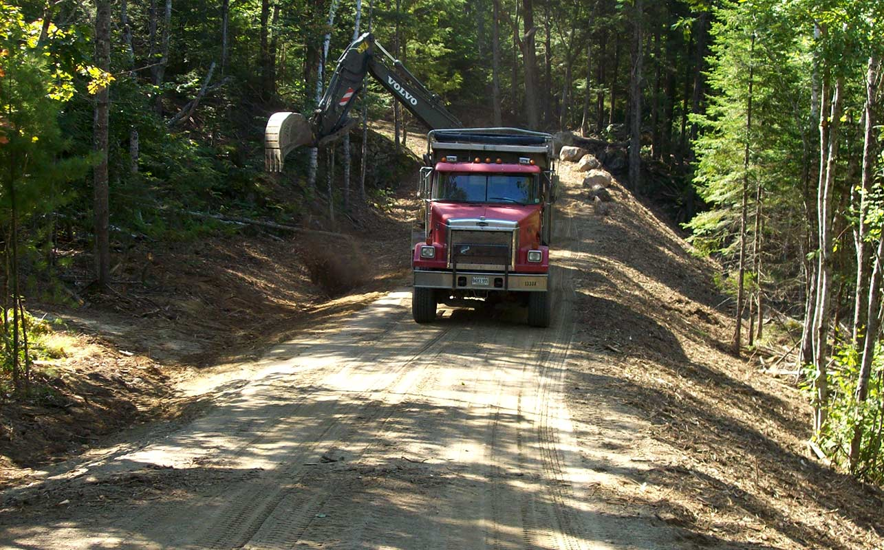 Long road/driveway construction in wooded area. Maine